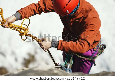 A rock climber works with a rope on the route, close-up. Face is not visible.