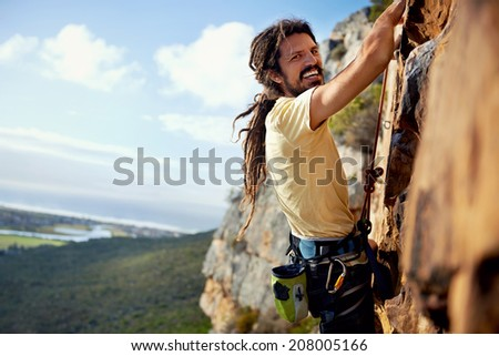 A rock climbing man with dreadlocks smiling at the camera while climbing up a steep mountain with a harness - stock photo