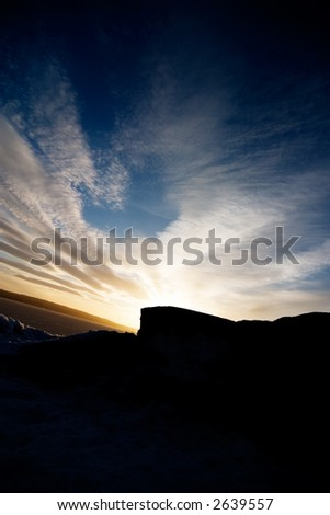 A rock landscape near the ocean during a sunset and a dramatic sky. - stock photo