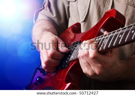 A rock lead guitarist  in action on stage - stock photo