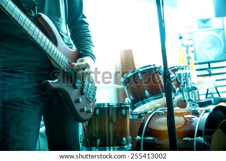 A Rock musician playing bass in the rehearsal Studio. - stock photo