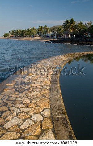 A rock path separates the sea from a salt water pool - stock photo