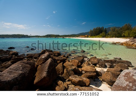 A rocky portion lines the perfect white sand beach and transparent clear waters of Koh Lipe, Thailand (aka Ko Lipeh). - stock photo