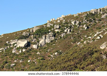 A rocky rolling green hill.  - stock photo