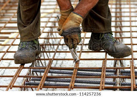 A rodbuster or iron worker working on a reinforcing rebar - stock photo