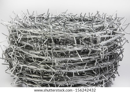 A roll of barbed wire over white background  - stock photo