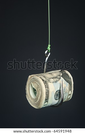 A roll of cash on a fishhook against a dark gray gradient backdrop. - stock photo