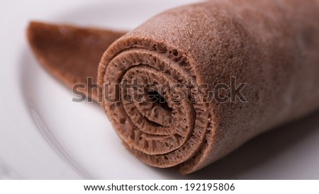 A Roll of Injera made from black teff on a white plate - stock photo