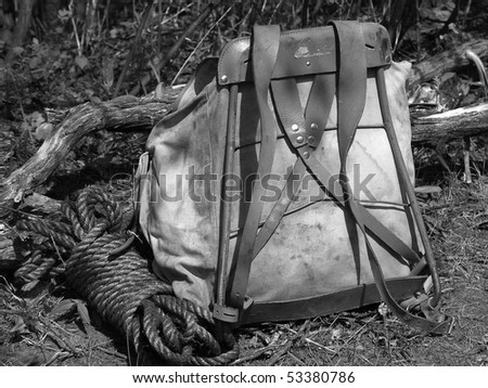 A roll of manila rope next to an old backpack with an A frame. - stock photo