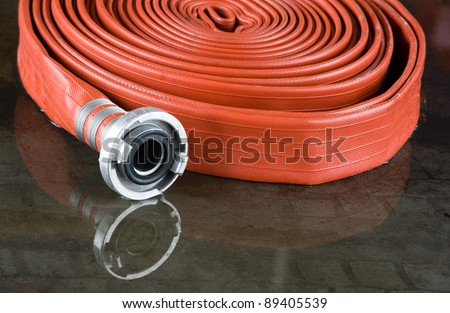 A rolled up firehose on the wet floor in a fire station used by firefighters - stock photo
