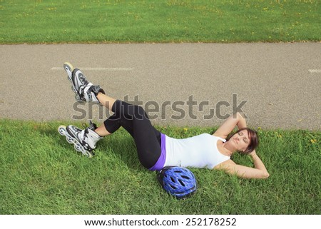 A Roller skating girl in park rollerblading on inline skates. - stock photo