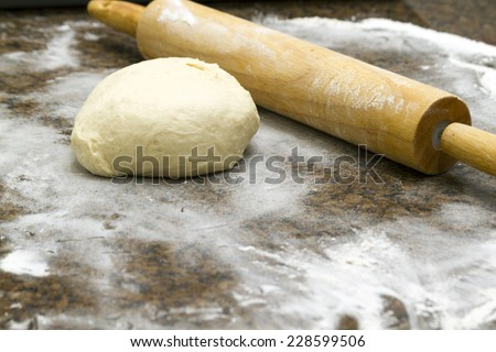 A rolling pin on the table with piece of flour mixed - stock photo