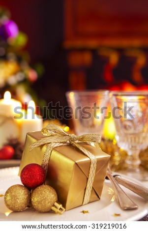 A romantic Christmas dinner table setting with candles and Christmas decorations. A fire is burning in the fireplace and Christmas stockings are hanging on the mantelpiece. - stock photo
