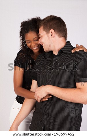 A romantic couple with a white man and a black woman, embracing and smiling with eye contact