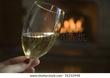 A romantic glass of white wine, or chardonnay, by a lit Spanish fireplace. - stock photo
