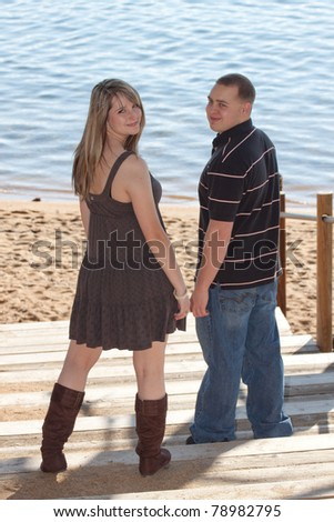 A romantic image of a cute couple on the beach in Lake Tahoe. - stock photo