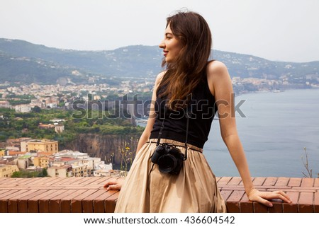 A romantic looking photographer girl traveling in Europe Italy and enjoying views and landscapes in the summer. - stock photo