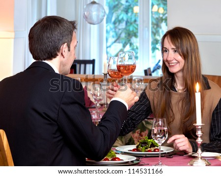 A romantic middle-aged couple enjoying a candlelit dinner raise their wine glasses in a toast to the future - stock photo