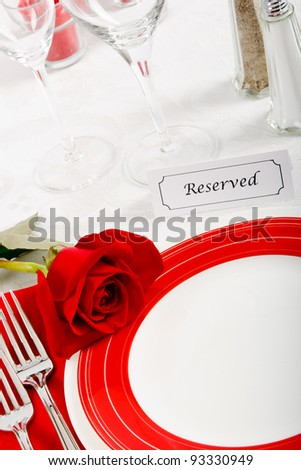A romantic red and white place setting shows a reserved table at an elegant restaurant ready to celebrate an anniversary or Valentine's Day. - stock photo