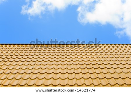 a roof is cover a yellow wavy metal on a background blue sky with white clouds