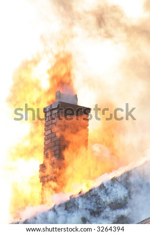 A roof top and chimney engulfed with fire - stock photo