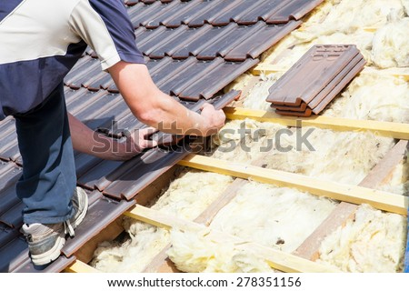 a roofer laying tile on the roof - stock photo