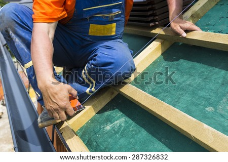 A roofer on the rooftop prepairing wooden construction. Measuring for better accuracy. - stock photo