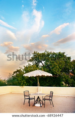 A rooftop getaway at sunset, with a table, two chairs and an umbrella.  Beautiful sky and clouds are in the background - stock photo