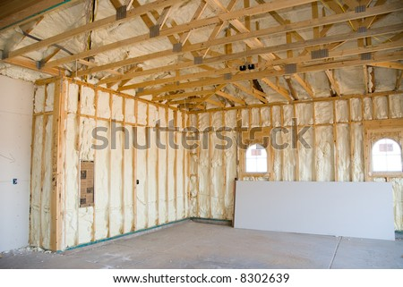 A room at a newly constructed home is sprayed with liquid insulating foam before the drywall is added. - stock photo