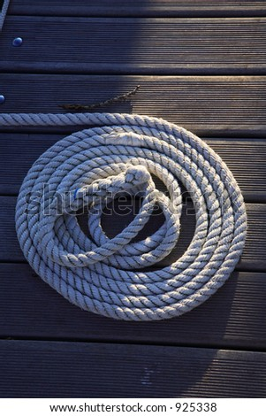 A rope on a wood port is half lighting by the evening sun.