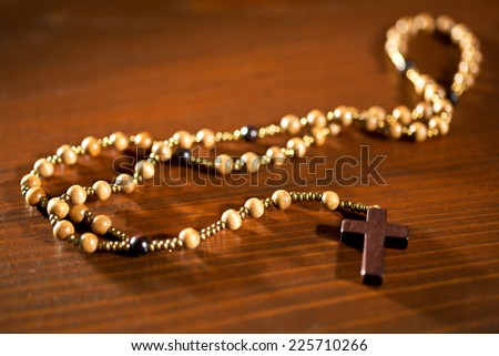 A rosary on the brown wooden table