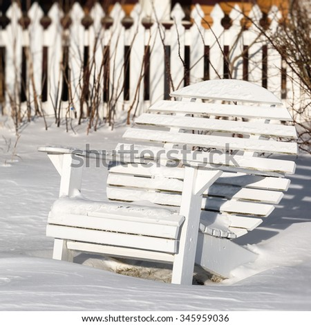 A round back Adirondack chair fondly know as a moon chair in the winter garden. - stock photo