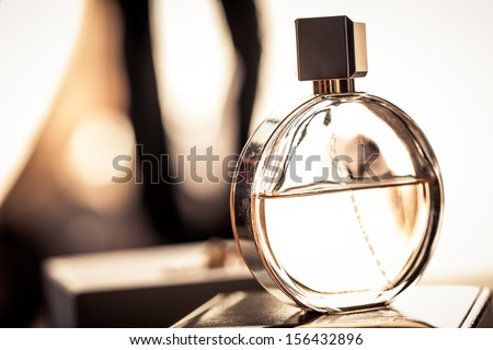 a round bottle of woman's fragrance resting on a box in light shining in from a window - stock photo