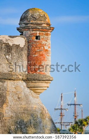 A round corner sentry box, on an old St. Augustine, Florida Spanish coquina stone fort called the Castillo de San Marcos, is backed by the tall masts of a Spanish Galleon in Matanzas Bay. - stock photo