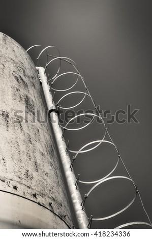 A round ladder climbing a silo in concrete, monochromatic. - stock photo