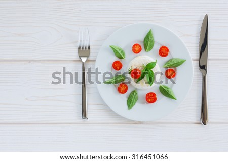 a round piece of cheese with basil and cherry tomatoes on a white plate with a fork
