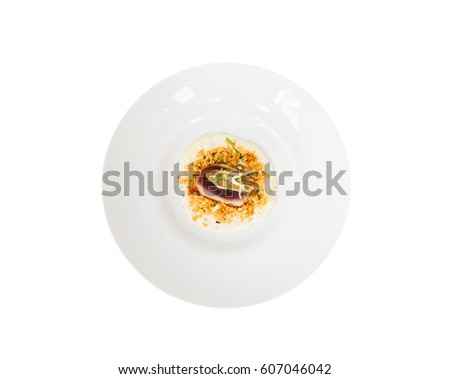 A round plate against a white background with spicy, steamed tuna fish fillet with pasta and lightly fried strips of celery.