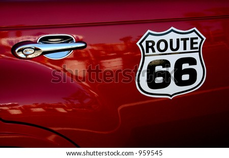 A Route 66 sign on the side of a PT Cruiser. - stock photo