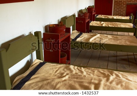 A row of beds in soldiers' quarter in 1820s. More with keyword Series08B. - stock photo