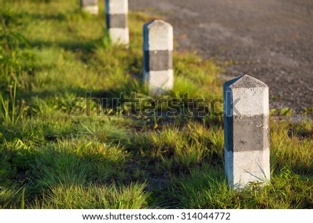 A row of black and white roadside pillars in a rural landscape - stock photo