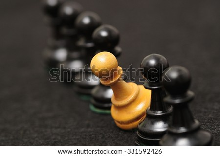 A row of black chess pieces consisting of black and only only white pawn. Only the white pawn is in focus