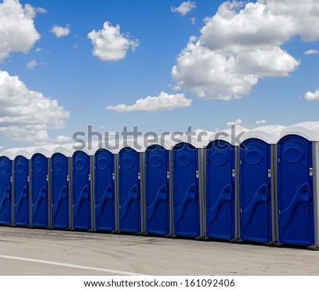 A row of blue portable toilets - stock photo