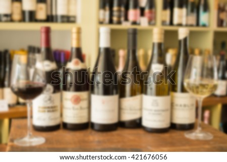 A row of bottles of wine between two wineglasses on wooden surface and wine collection in the background.