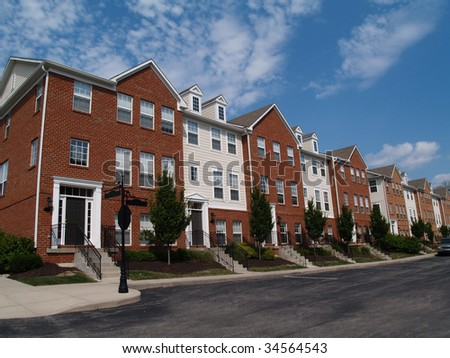 A row of brick condos or townhouses beside a street. - stock photo
