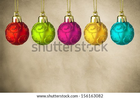A row of brightly coloured Christmas baubles with swirly glitter patterns and gold clasps, hanging from gold strings in a row on a parchment background with copy space below. - stock photo