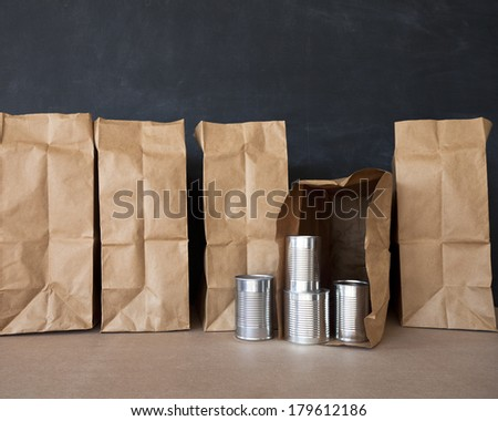A row of brown bags and some tin cans against a black board. - stock photo