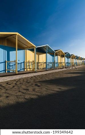 A row of colored cabins on the beach on a sunny day.