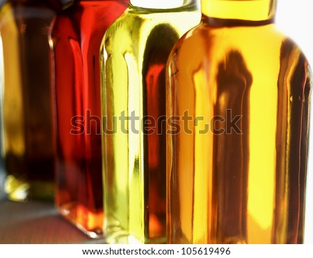 a row of colored oil bottles on a green herringbone fabric in landscape - stock photo
