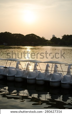A row of colorful pedal boats on a lake at sunset