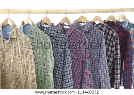A row of colorful row shirts hanging on hangers on a white background - stock photo